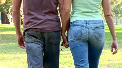 stock-footage-young-couple-walking-and-holding-hands-in-park
